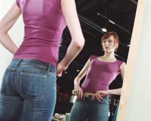 Young woman trying on jeans in front of mirror, low angle view